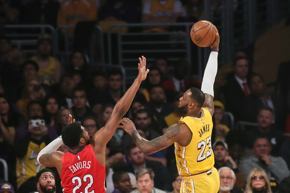 Los Angeles Lakers forward LeBron James with a sky hook over New Orleans Pelicans forward Derrick Favors.